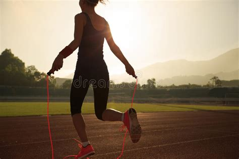 Woman Skipping Rope During Sunny Morning Stock Photo